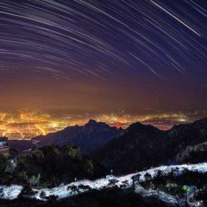 """Piąte miejsce w kategorii """"Against the Lights"""" zajęło zdjęcie """"Heavenly Street """" (Niebiańska ulica), autorstwa Chińczyka Song Hongxiao. Ta sekwencja fotograficzna w długiej ekspozycji, zrealizowana 30 marca 2013 r., ukazuje smugi gwiazd z chińskiej świętej góry Tai Shan. Autor wyjaśnia: """"Według starożytnej tradycji chińskiej, ludzie wchodzą na szczyt góry, aby się modlić przed wschodzącym Słońcem. Na tym zdjęciu tysiące ludzi przemierza niebiańską ulicę. Błyski fleszów ich aparatów fotograficznych stanowią kontrapunkt dla gwiazd na niebie"""". Autor: Song Hongxiao Zdjęcie: Heavenly Street"""