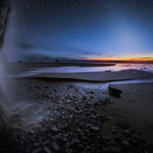 """Na drugim miejscu w kategorii """"Beauty"""" (Piękno) uplasowało się zdjęcie Bena Coffmana z Portland, USA, """"False Dusk and Falls at Oregon Coast"""" (Fałszywy zmierzch i wodospady na wybrzeżu Oregonu), wykonane w lutym 2014 z Hug Point na wybrzeżu Pacyfiku, w północnym stanie Oregon. Fotograf uchwycił na tle kaskady rozbijającej się o brzeg morski i blasku wieczornych gwiazd, granicę dzielącą dzień od nocy, moment przejścia dnia w noc - światło zodiakalne, światło słoneczne odbite od cząstek pyłu kosmicznego, wytwarzanego przez asteroidy i komety. Jest to fascynujące zjawisko nocnego nieba znane również jako """"fałszywy świt"""", obserwowane wyłącznie w ciemności po zachodzie słońca lub przed brzaskiem w pasie przebiegającym wzdłuż ekliptyki - zodiaku - w pobliżu Słońca.  Autor: Ben Coffman Zdjecie: False Dusk and Falls at Oregon Coast"""