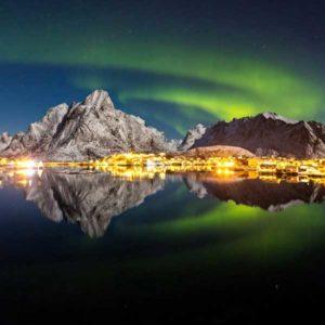 """""""Reflected Aurora"""" (Refleksy zorzy polarnej) rumuńskiego fotografa Alexa Conu zostało wyróżnione drugą nagrodą w kategorii """"Lights"""" (Światła). Zdjęcie zostało zrobione w noc księżycową 15 marca 2014 r. na Lofotach, wyspach w północnej Norwegii, po kilku dniach burzy, kiedy to zorza powróciła na niebo Reine, malowniczej wioski rybackiej. Na tej fotografii widać połączenie dwóch wielkich sił: świateł wioski biegnących wzdłuż wybrzeża fiordowego, oddzielających niebo od tafli wody oraz zapierającej dech w piersiach zorzy nad górami. Dodatkowy walor zdjęciu nadaje blask księżyca odbijający się od śniegu.  Autor: Alex Conu Zdjęcie: Reflected Aurora"""