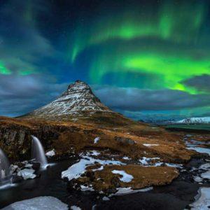 """Trzecie miejsce w kategorii """"Beauty of the Night Sky"""" zajął Austriak Nicholas Roemmelt za """"Kirkjufell Nights"""" (Noce Krikjufell), wyjątkowe zdjęcie zorzy polarnej nad wodospadami w pobliżu islandzkiej góry Kirkjufell, zrobione w noc księżycową w marcu 2014 r. Sugestywną moc temu zdjęciu nadaje ukazanie cudownego współistnienia sił natury w tym małym zakątku wszechświata: kaskad kształtujących skalisty krajobraz, góry opierającej się erozji i zorzy polarnej opasującej biegun na tle gwiazd na niebie. Autor: Nicholas Roemmelt Zdjęcie: Kirkjufell Nights"""
