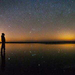 """Trzecie miejsce w kategorii """"Against the Lights"""" zajął irański fotograf Majid Ghohroodi za zdjęcie """"Unlimited Sky"""" (Niebo bez granic) zrealizowane w lutym 2014 r. nad słonym jeziorem na pustyni Maranjab, w pobliżu miasta Kashan. Rozgwieżdżone nocne niebo z konstelacją Oriona pośrodku zlewa się z kopułami świetlnymi trzech dużych miast na horyzoncie. Światło gwiazd odbite od wody jest spolaryzowane i dlatego odbity obraz jest jaśniejszy niż obraz nieba. Zdjęcie to ukazuje graficznie niesamowity zasięg nocnych świateł, które rozchodzą się daleko poza miasta na odległe przestrzenie.  Autor: Majid Ghohroodi Zdjęcie: Unlimited Sky"""