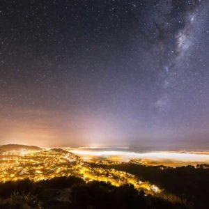 """Czwarte miejsce w kategorii """"Against the Lights"""" przyznano zdjęciu """"Fog Below and The Stars Above""""  (Poniżej mgła, powyżej gwiazdy) Nowozelandczyka Marka Gee. Ten wspaniały krajobraz nocny, uchwycony w marcu 2013 r.,  pokazuje gęstą mgłę spowijającą Wellington, stolicę Nowej Zelandii. Wyjaśnia fotograf: """"Mgła rozprzestrzeniała się i tłumiła miejskie światła, co umożliwiło mi sfotografowanie miasta i Drogi Mlecznej w pojedynczej ekspozycji. Zwykle nie jest to możliwe, ze względu na intensywne światło płynące od sztucznego oświetlenia"""". Autor: Mark Gee Zdjęcie: Fog Below and The Stars Above"""
