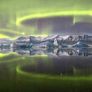 Jaskrawozielona aurora borealis uchwycona w islandzkim parku narodowym Vatnajökull odbija się w prawie idealnej symetrii w jeziorze lodowcowym Jökulsárlón powstałym z wody z topniejącego lodowca Vatnajökull. Całkowity brak wiatru i prądów tworzy zjawiskowy efekt lustrzanego odbicia, dzięki któremu obraz przywołuje uczucie absolutnego spokoju. Paradoksalnie jednak, łuki i spirale zorzy kształtowane są przez niesamowity ruch cząstek podporządkowanych zmiennemu polu magnetycznemu Ziemi. Autor: James Woodend (UK) Zdjęcie: Zorza polarna nad jeziorem lodowcowym