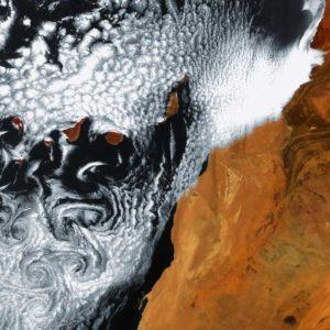 """Ścieżka wirów von Karmana powstaje, kiedy strumień powietrza, w wyniku napotkania na przeszkodę w postaci wysokiego wzniesienia, wzburza się, tworząc w chmurach symetryczne wiry. Na tym zdjęciu wiatr wiejący z północy """"starł się"""" z wyspami i zwija chmury w kształt spirali. Dzięki uprzejmości: ESA"""